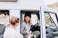 Two friends talking at camper van containing outdoor, sport, and active