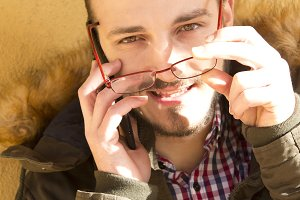 Young man with glasses talking on mobile phone