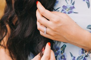Beautiful girl are touching by her hand's long, black and curly hair. Close-up.