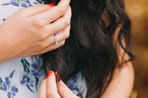 Beautiful woman are touching by her hand's long, black and curly hair