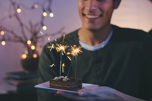 Young man looking at cake with spark