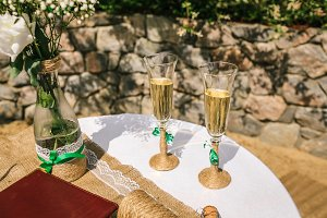 Two decorated glasses of champagne on the table in the yard at the wedding ceremony
