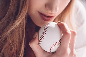young woman holding baseball ball
