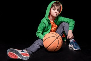 boy sitting with basketball ball
