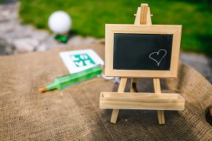 Blank chalkboard with wooden tripod in wedding ceremony with outdoor and garden style