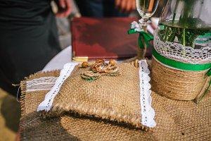 Wedding rings laying on decorative cushion of burlap