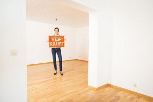 Realtor In Empty Apartment, Holding 'verkauft' Sign