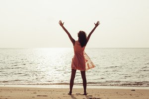 Woman enjoying freedom feeling happy at beach at sunset