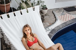 Woman laying down on white hammock