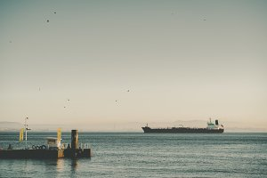 Cargo barge on sunset in distance