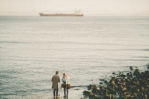 Couple near river with cargo ship
