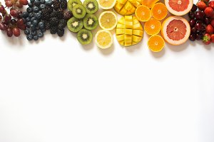 Top view rainbow fruits on white