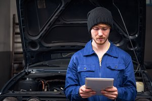 Mechanic Checking A Car Engine Using Digital Tablet