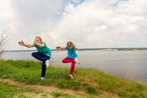 Preparation of yoga classes. Mom and daughter are practicing yoga on the river bank. Recreation. Sport. Health.