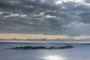 River landscape. Island in the middle of the river. Wide river. Dnieper. A ray of the sun through the clouds.