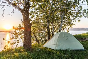 Sunrise over the river. Tourist tent. River bank.