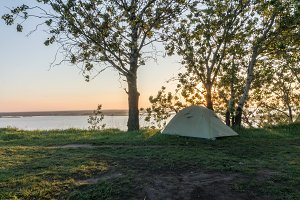 Tourist tent on the river bank. Landscape, river, morning.