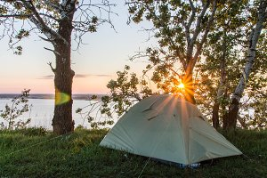 Tourist tent against the background of the rising sun. Sunrise over the river. Dnieper. Rzhishchev. Ukraine.