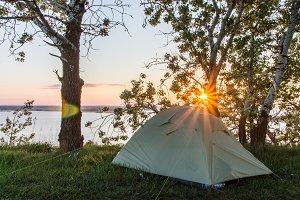 Tourist tent against the background of the rising sun. Sunrise over the river. Dnieper. Rzhishchev. Ukraine.