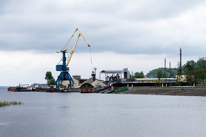 Container operation in port. The lifting crane pours sand in the river port.