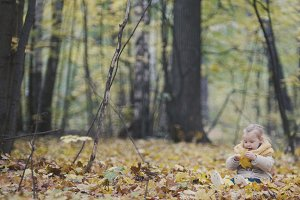 Little happy baby girl plays in autumn park among yellow leaves - wide angle