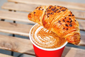 Cup with coffee and croissant