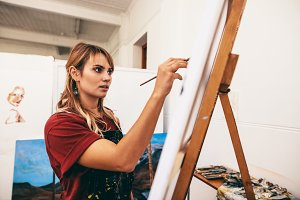 Woman painter painting on canvas