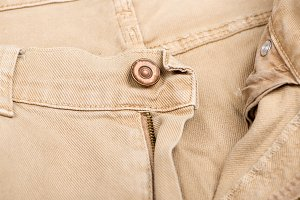Close-up of the zipper and a button of brown jeans. Horizontal studio shot.