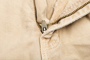 Close-up of the zipper of brown jeans. Horizontal studio shot.