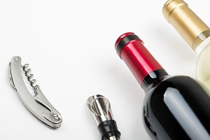 Top view of corkscrew on white background next to several corks. Horizontal studio shot. Isolated.