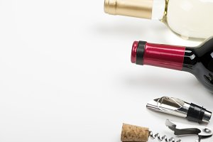 Corkscrew next to two bottles of white wine on white background. Horizontal studio shot. Isolated.
