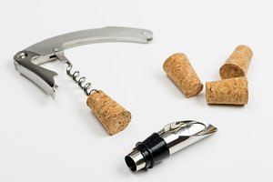 Close-up of corkscrew on white background next to several corks. Horizontal studio shot. Isolated.