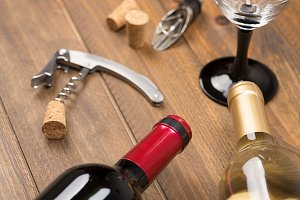 Corkscrew next to a two bottles of wine and a glass on wooden table. Horizontal studio shot.