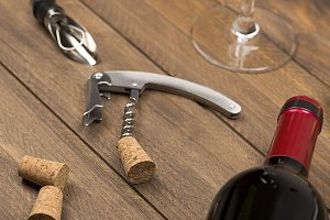 Corkscrew next to a bottle of wine and a glass. Horizontal studio shot.