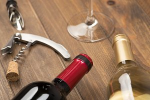 Corkscrew next to a two bottles of wine and a glass. Horizontal studio shot.
