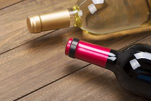 Close up of two wine bottles on brown wooden table.