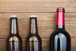 Top view of two beer bottles and a wine on wooden table.