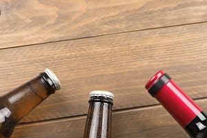 Top view of two beer bottles and a red wine on wooden table. Copy space.