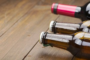Close-up of two beer bottles and one wine on wooden table. Copy space.