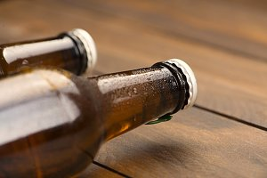 Close-up of two bottles of beer on the wooden background. Copy space.