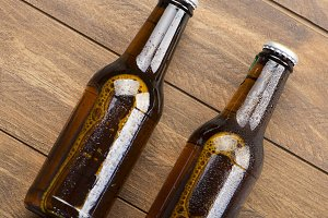 Horizontal shot of beer bottles on the wooden background. Copy space.