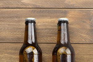 Horizontal shot of two beer bottles on the wooden background. Copy space.