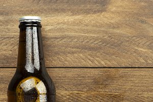 Horizontal shot of beer bottle on the wooden background. Copy space.