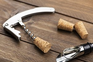 Close-up of corkscrew on on wooden table next to several corks. Horizontal studio shot.