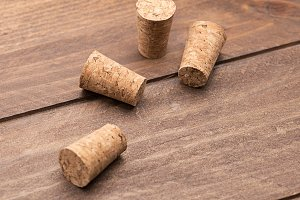 Close-up of corks on brown wooden table. Horizontal studio shot.