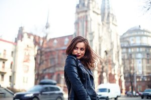 young beautiful brunette walking the city.leather jacket,urban backpack , bright red lips The concept of street fashion.