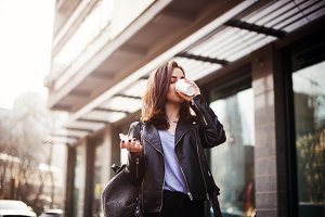 Close up fashion street style portrait of a beautiful girl in a casual outfit walks in the city . Beautiful brunette drinking coffee