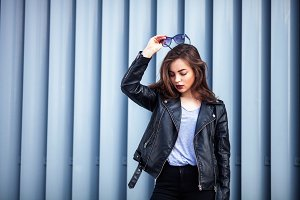 Fashion hipster woman posing outdoor. leather jacket,brunette hair, bright red lips, sunglasses.Street fashion concept.