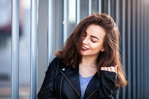 Amazing joyful pretty girl with long brunette hair. posing outdoor. leather jacket,brunette hair, bright red lips Close up fashion street stile portrait
