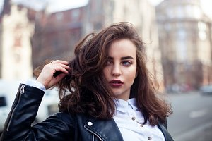Amazing joyful pretty girl with long brunette hair. posing outdoor. leather jacket,brunette hair, bright red lips